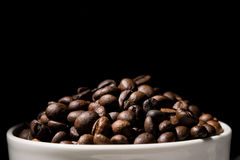 Koffiemok met koffiebonen wordt gevuld over zwarte achtergrond die Stock Afbeeldingen