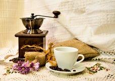 Koffiemolen met jutezak van geroosterde bonen en witte kop van koffie op het witte gebreide linnentafelkleed Stock Foto's