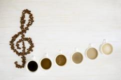 Koffienota's Gebraden koffiebonen in de vorm van een g-sleutel, zes koppen van verschillende koffie zoals nota's stock afbeeldingen