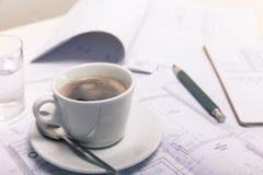 Koffiepauze bij de architectendesktop Stock Afbeelding