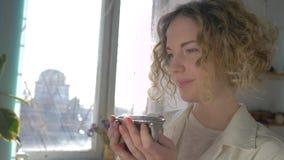 Koffiepauze van gelukkige glimlachende schildersvrouw die met kop hete drank van creatief proces genieten tegen zonovergoten vens stock footage