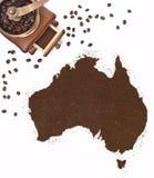 Koffiepoeder in de vorm van Australië en een koffiemolen (serie Stock Afbeelding