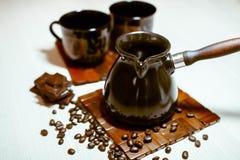 Koffiepot met koffiebonen, koppen en chocolade Stock Fotografie