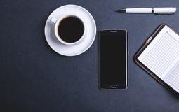 Koffiesmartphone en notitieboekjes stock foto