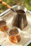 Koffievoorbereiding in koperpot met heet gouden zand openlucht Stock Fotografie