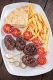 Kofta kebab with french fries and pita bread Stock Photos