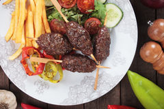 Kofta kebab with french fries. Kofta kebab, turkisg minced meat skewer with french fries and vegetable salad Royalty Free Stock Image