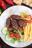 Kofta kebab with french fries. Kofta kebab, turkish minced meat skewer with french fries and vegetable salad Stock Image