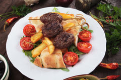 Kofta kebab with fried potatoes and flatbread Royalty Free Stock Image