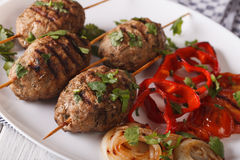 Kofta kebab with grilled vegetables on a plate close-up. horizon Royalty Free Stock Photos