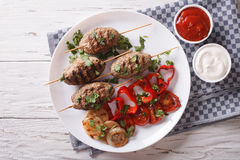 Kofta kebab with grilled vegetables on a plate and sauce. horizo Royalty Free Stock Images