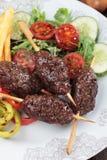 Kofta kebab, ground beef skewer. Kofta kebab, oriental minced meat skewer with salad and grilled vegetable Stock Photos