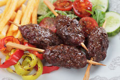 Kofta kebab minced meat barbecue. Kofta kebab, oriental ground beef skewer with french fries and grilled vegetable Royalty Free Stock Images