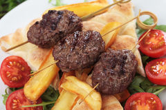 Kofta kebab, minced meat skewer. Kofta kebab, oriental minced meat skewer with salad and french fries Stock Photo