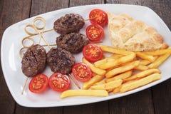 Kofta kebab with pita bread and french fries. Kofta kebab, turkish minced meat skewer with pita bread and french fries Stock Image