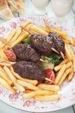 Kofta kebab skewer. Kofta kebab, turkish minced meat skewer with salad and french fries Stock Photography