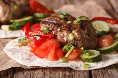 Kofta turco con gli ortaggi freschi su una fine piana del pane su Uff Immagine Stock