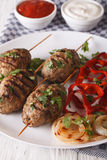 Kofte kebab with grilled vegetables on a plate and sauce close-u Stock Photos