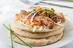 Kofte pita. Shish kofte (kofta kebab) Muslim street food with vegetables and herbs on pita bread stock photography