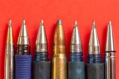 Kogel en pennen op rode achtergrond De persvrijheid is concept in gevaar het concept van de de vrijheidsdag van de wereldpers royalty-vrije stock afbeeldingen