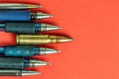 Kogel en pennen op rode achtergrond De persvrijheid is concept in gevaar het concept van de de vrijheidsdag van de wereldpers stock afbeelding