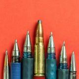 Kogel en pennen op rode achtergrond De persvrijheid is concept in gevaar het concept van de de vrijheidsdag van de wereldpers stock fotografie
