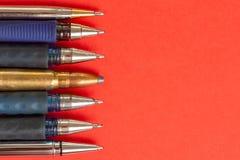 Kogel en pennen op rode achtergrond De persvrijheid is concept in gevaar het concept van de de vrijheidsdag van de wereldpers royalty-vrije stock afbeelding