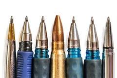 Kogel en pennen op witte achtergrond De persvrijheid is concept in gevaar het concept van de de vrijheidsdag van de wereldpers stock afbeelding