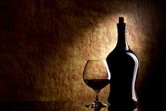 Kognak-Glas und Flasche auf einem alten Stein Stockfotografie