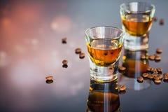 Kognak oder Likör, Kaffeebohnen und Gewürze auf einem Glastisch stockfotografie