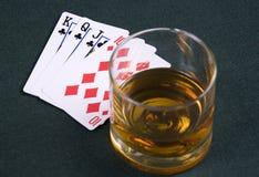 Kognak und Spielenkarten auf einer Tabelle für einen Schürhaken lizenzfreie stockbilder