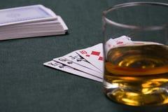 Kognak und Spielenkarten auf einer Tabelle für einen Schürhaken Stockbild