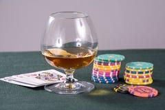 Kognak und Spielenkarten auf einer Tabelle für einen Schürhaken stockfotografie