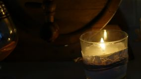Kognakglas am Kerzenlicht mit hölzernen Fässern am romantischen Abend Langsame Bewegung stock footage