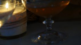 Kognakglas am Kerzenlicht mit hölzernen Fässern am romantischen Abend Langsame Bewegung stock video