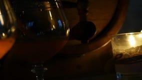 Kognakglas am Kerzenlicht mit hölzernen Fässern am romantischen Abend Langsame Bewegung stock video footage