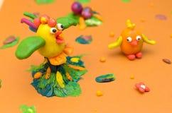 Kogut i kurczak od plasteliny na żółtym tle Obrazy Royalty Free