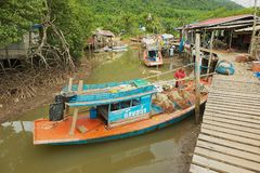 View to the fishermen`s village with stilt residential houses and fishing boats at low tide in Koh Chang, Thailand. Royalty Free Stock Image