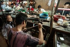 Goldsmith melts the gold with gun fire lighter welding to create precious accessory. Koh Kong Market. Koh Kong Province, Cambodia royalty free stock photo