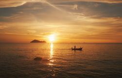 Koh Phangan island, Thailand. Sunset on the sea. Fisherman in a boat royalty free stock image