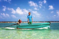 Koh Phangan, Thaïlande - 29 janvier 2014 : Le pêcheur thaïlandais heureux navigue sur le canot automobile à travers la plage de N Image libre de droits