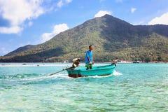 Koh Phangan, Thaïlande - 29 janvier 2014 : Le pêcheur thaïlandais heureux navigue sur le canot automobile à travers la plage de N Images libres de droits