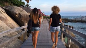 Koh Phangan, Thailand- 20 DEC 2016: Two female best friends talking and walking at wooden island bridge. Koh Phangan, Thailand- 20 DEC 2016: Two female friends stock video