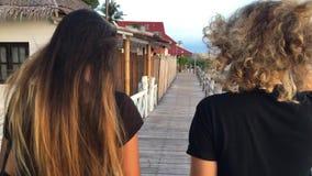 Koh Phangan, Thailand- 20 DEC 2016: Young girls making conversation and walking at wooden bridge. Back slowmotion closeup view. Koh Phangan, Thailand- 20 DEC stock footage