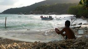 KOH PHANGAN, THAILAND - 11. JANUAR 2019 hängender Köder des ethnischen Fischers auf Netz Seitenansicht des ethnischen hemdlosen M stock video footage