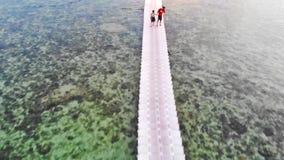 Koh Phangan, Thailand, 21 kan 2018 Het vliegen over pijler met mensen die op brug onder het overzees op tropisch eiland lopen stock videobeelden