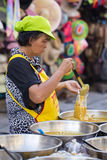 Thai woman prepares and sells food on the traditional street market in Koh Phangan, Thailand. KOH PHANGAN, THAILAND - NOVEMBER 26, 2016 : Thai street vendor Royalty Free Stock Image