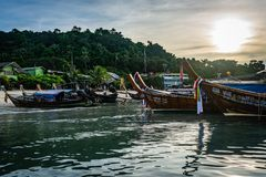 KOH PHI PHI, THAILAND - NOVEMBER 2018: Boats lined up at the edge of the island at dawn, morning sun in the sky, green trees and p royalty free stock photography