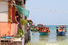 Koh Rong wyspa, Kambodża - 07 2018 Kwiecień: denny widok z łodzią, domem na stosach i kobiety podlewaniem, kwitnie Fotografia Royalty Free
