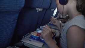 Young girl in the headphones is eating a delicious breakfast on board the Bangkok Airways stock footage video stock video footage